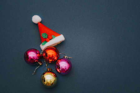 Christmas ornament balls and santa hat on grey background. Stock Photo
