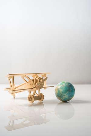 Wooden Aeroplane toy with world globe on white background.Travel Concept. Stock Photo