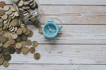 jar of coins with analog alarm clock on vintage wooden table.Financial and investment concept. 版權商用圖片