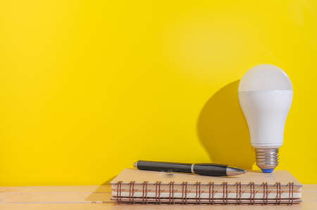 Blank notebook and White bulb on yellow background.Minimal idea concept. Imagens