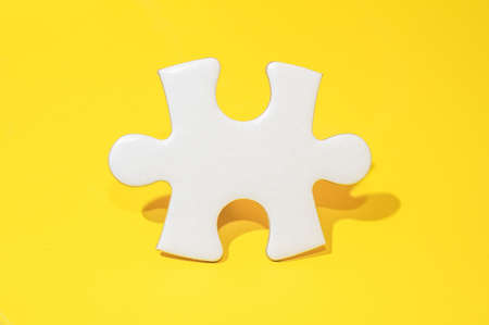 A piece of Blank white puzzle on yellow background with copy space.Problem and solution concept. Banco de Imagens