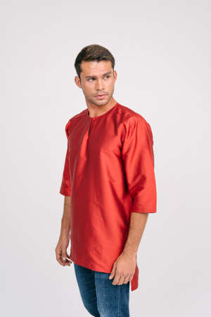Handsome young Asian male wearing Baju Melayu isolated over white background.Modern fashion for Eid ul Fitr.