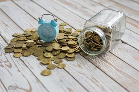 jar of coins with analog alarm clock on vintage wooden table.Financial and investment concept. Фото со стока