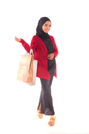 Young female model holding shopping bag isolated over white background.