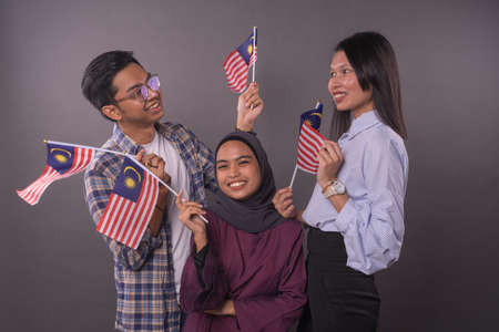 Happy multi racial Malaysian people holding Malaysia Flag.Independence day and patriotic concept.Studio shot.