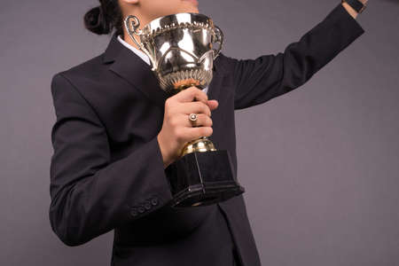 A young business man holding a gold trophy and celebrate his archivement.Close up shot Stock fotó