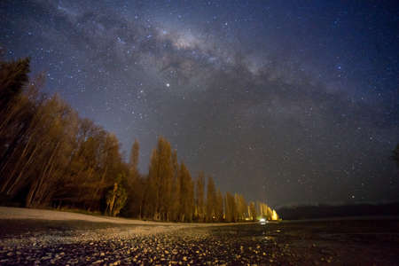 Amazing milky way view at pine forest on the mountain.Huge amount of grain effects due to super low light shot.Soft focus image due to very slow shutter shot. 免版税图像