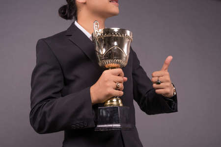 A young business man holding a gold trophy and celebrate his archivement.Close up shot Foto de archivo