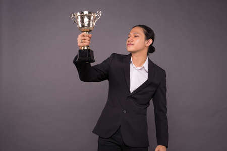 A business man holding a gold trophy and celebrate his archivement.