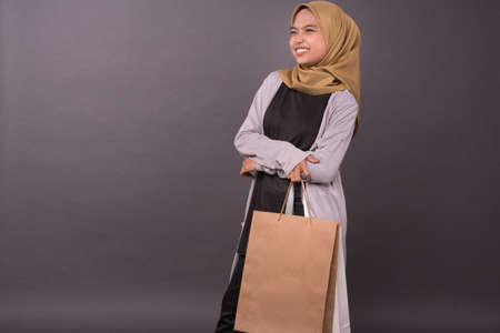 Happy malay girl holding shopping bags.