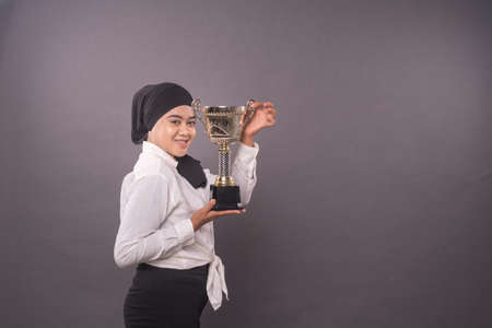 Happy young female studentor business woman holding his gold trophy and celebrating her victory.Studio shot. 写真素材