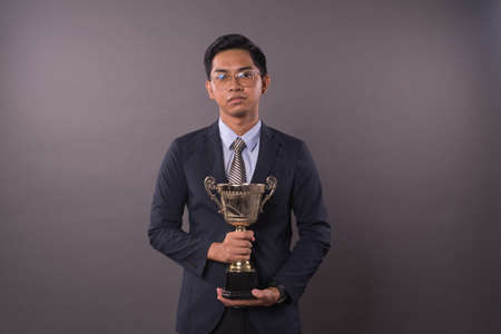 Happy young Asian male student or business man holding his gold trophy.Studio shot. 写真素材