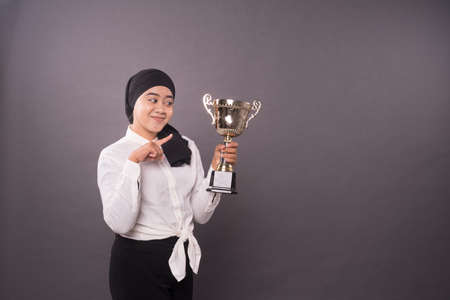 Happy young female business woman holding his gold trophy and celebrating her victory.Studio shot. 写真素材