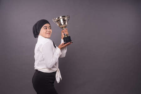 Happy young female business woman or student holding his gold trophy and celebrating her victory.Studio shot.