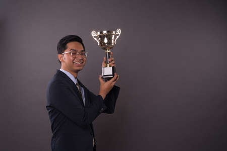 Happy young male business man holding his gold trophy and celebrating his victory.Studio shot.