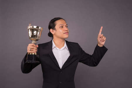 Successful glory.Young business man holding a gold trophy and celebrate his archivement.