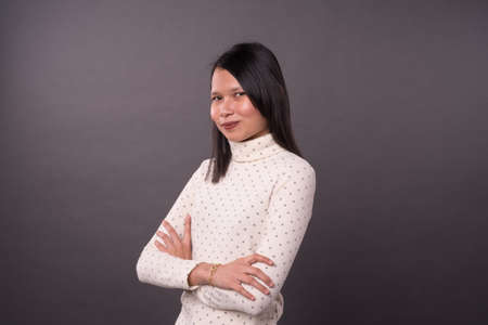 Portraiture of adult Chinese woman over grey background. 写真素材