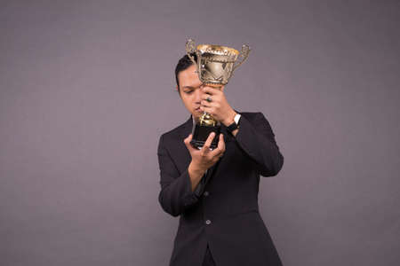 Young business man holding a gold trophy and celebrate his archivement.