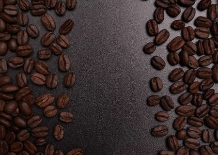 Close up shot of coffee beans on black board with copy space.