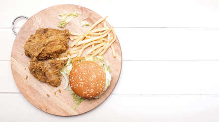 Fried chickens,cheese burger with fries on wooden chopping board isolated over white background.