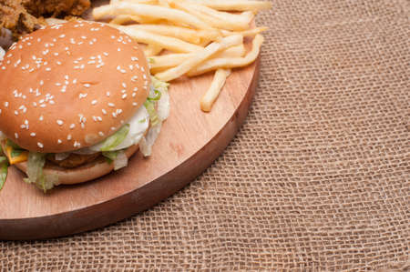 Fried chickens,cheese burger with fries on wooden chopping board with vintage canvas background.View from top.