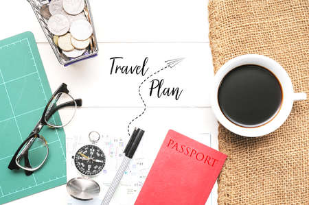 """Travel Tips concept.A compass ,book, passport and coffee cup on white desk written wioth text """"Travel Tips"""""""