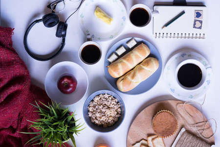 Top view of breakfast menu on white dining table.Coffee,milk, cereal, apple,cracker and bun on white table view from top.Food lay flat concept.