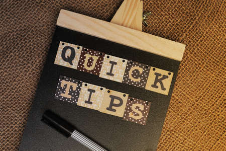 Alphabet wooden block forming word Quick Tips on chalkboard.