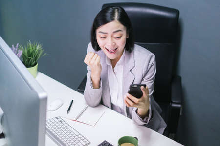 Happy chinese female worker at her office desk working on her computer. and smartphone.Excited face expression.