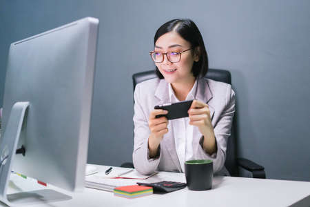 Happy chinese female worker at her office desk using her smart phone and smiling. 写真素材