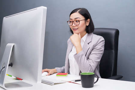 Happy chinese female worker at her office desk working on her computer.Happy girl at work drinking coffee.