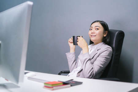 Happy asian female worker at having coffee at her office desk and smiling. 写真素材