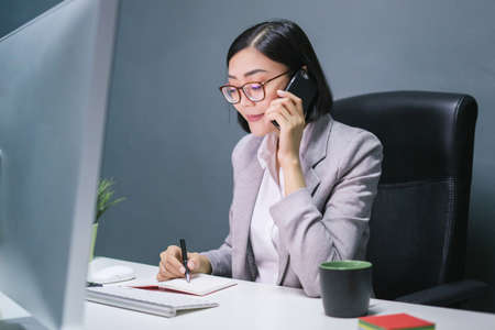 Happy chinese female worker at her office desk answering phone and smiling.Happy business woman. 写真素材