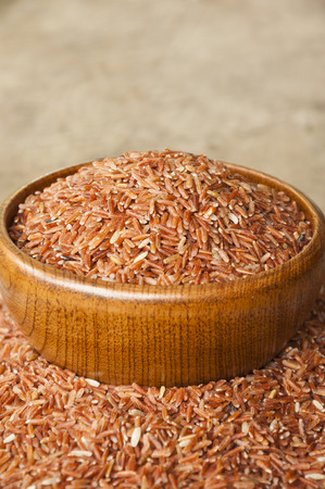 backgruond: Brown rice in wood cup have wood table is backgruond.