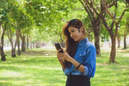 graden: Happy woman using a smart phone in the graden Stock Photo