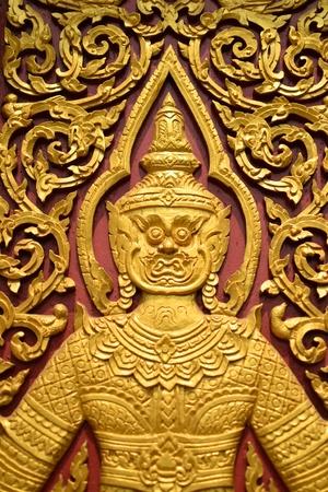 Laithai carved on the door atThai temple . Stock Photo - 13118189