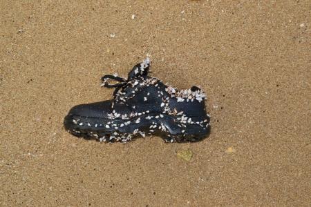 Old shoe on the sandy beach. photo