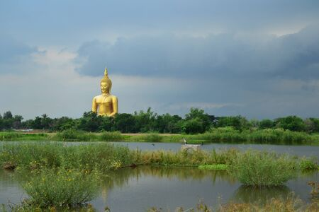 Natural pond in front of Statue of sitting buddha in Thai temple,Angthong Province,Thailand,Asia