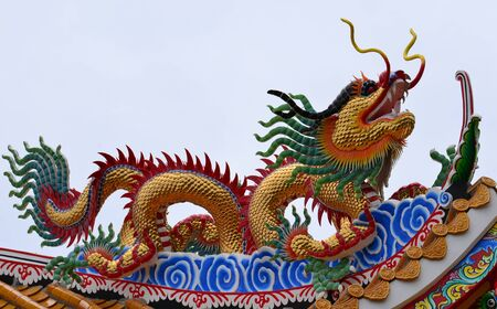 Golden Dragon. on the roof with blue sky at Chinese shrine ,Thailand. photo