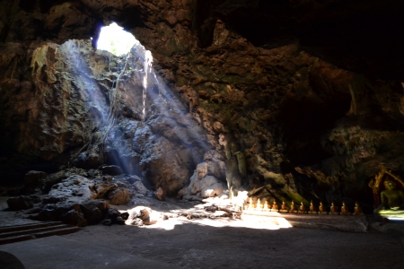 Buddha statue and Natural light inside the cave at Khaoluang, Phetchaburi Province, Thailand. photo