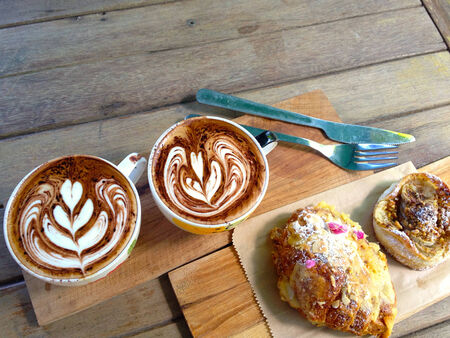 Coffee and desserts on the wooden desk. photo