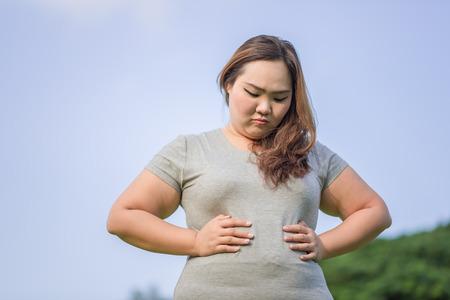 beautiful fat woman check her big paunch in the garden Standard-Bild