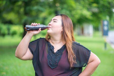 drinking soda: Fat woman drink cola in garden