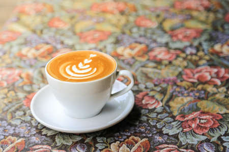 Coffee Latte on vintage tablecloth in morning Stock Photo