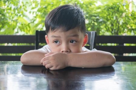 지루한 소년이 우울함을 느끼고 거의 자연 배경으로 울다.