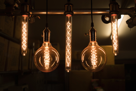 Close up group of hanging light bulbs with storage room background in darkness. Retro style