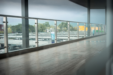 Long corridor with hardwood floor and car park background