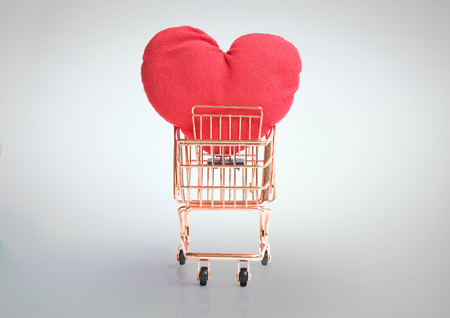 Front view of shopping cart with big red heart isolated and clipping path on grey background Imagens