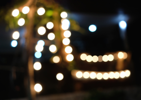 Defocused light decorated on woods in front of house