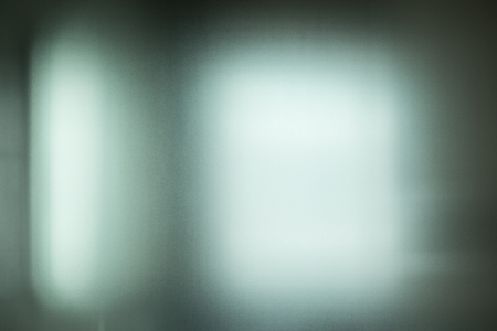 Light shining through blurred frosted window glass and mysterious concept background